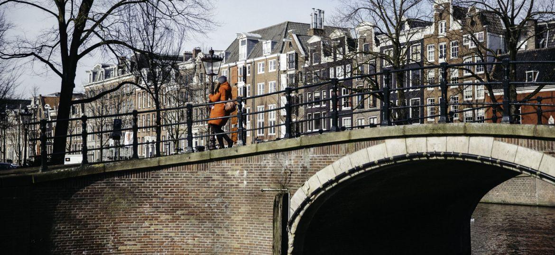girl-standing-amsterdam-canal-jordaaan-who-is-amsterdam