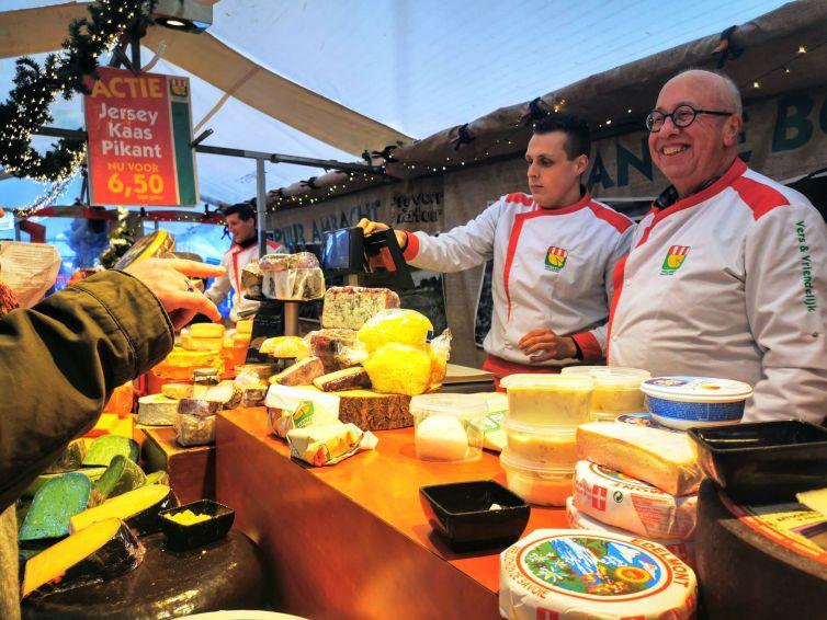 two cheese mongers selling gouda cheeses at noordermarkt amsterdam