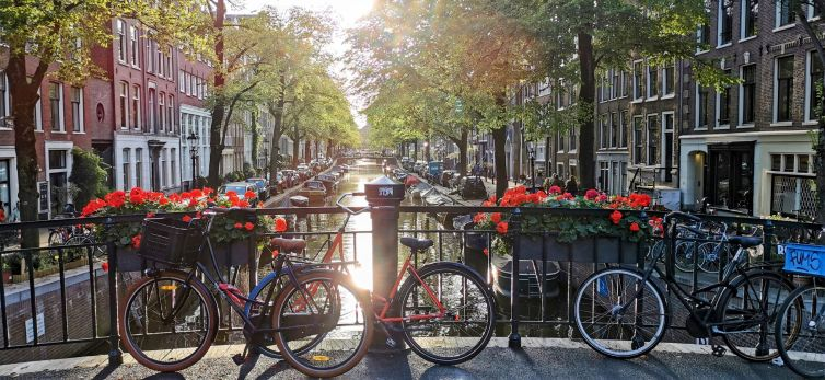 three bicycles parked by an amsterdam canal