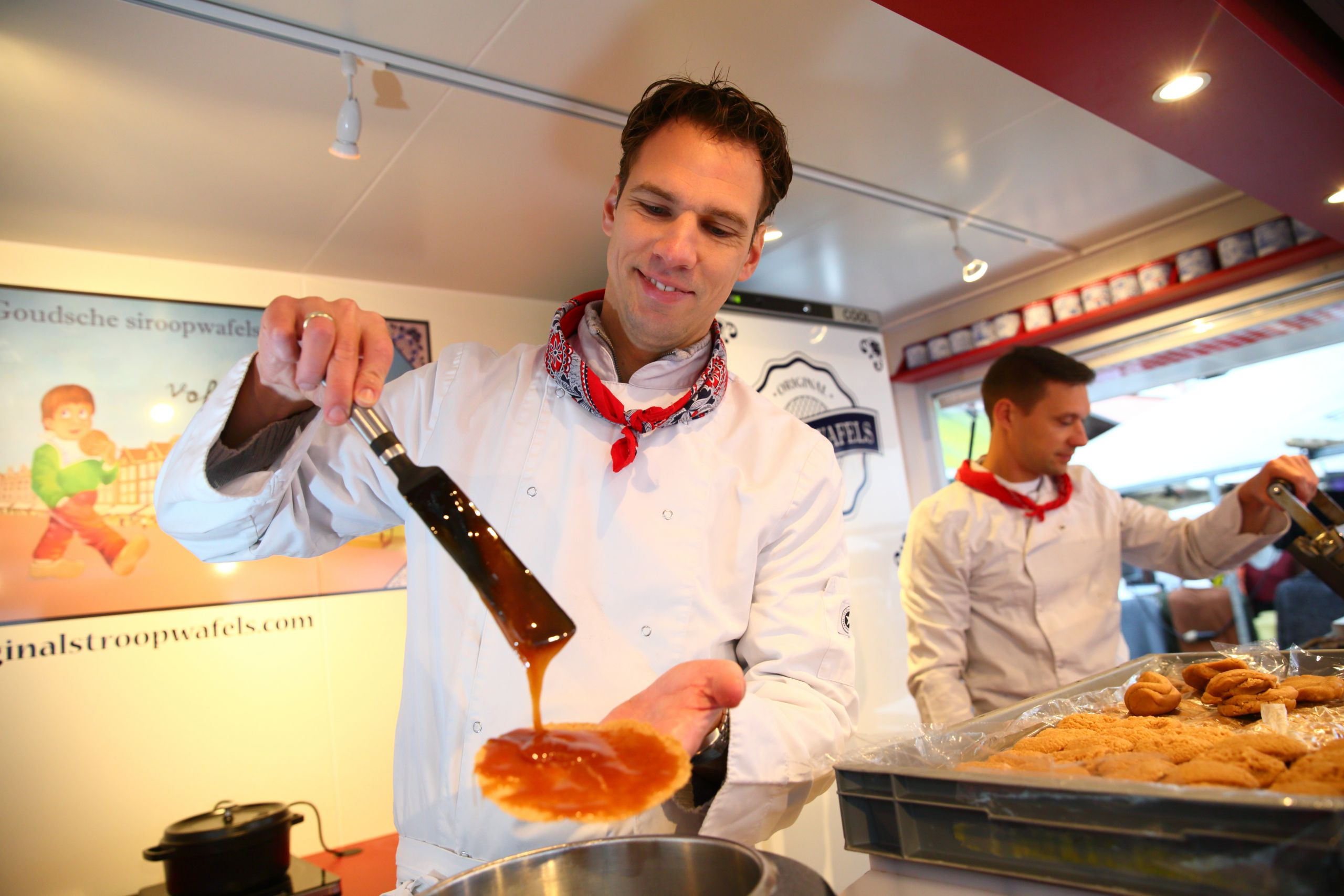 man pouring syrup on a dutch stroopwafel and another makes a fresh waffle at albert cuyp market