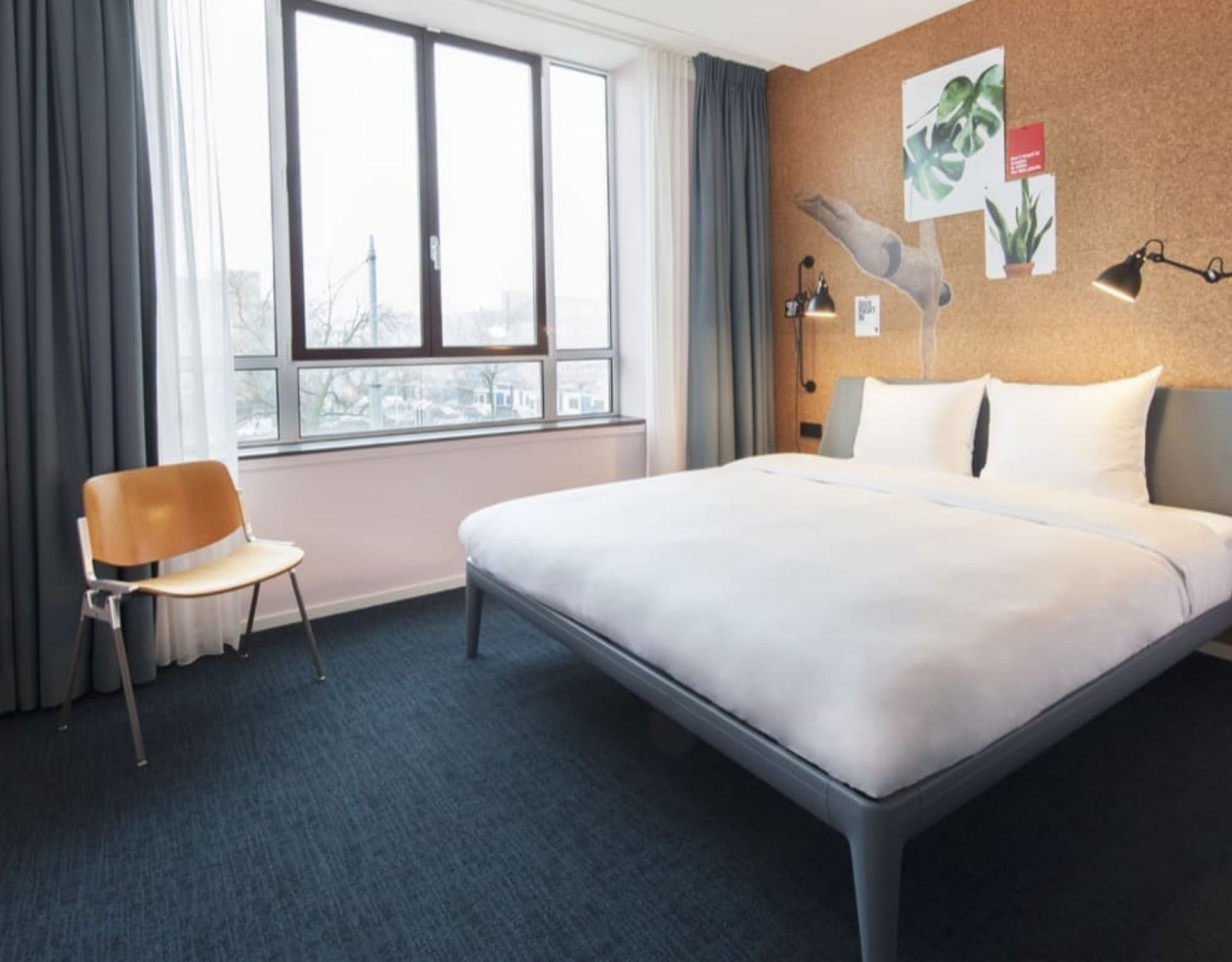 a queen-sized bed and chair with lamps in a hotel room conscious hotel amsterdam