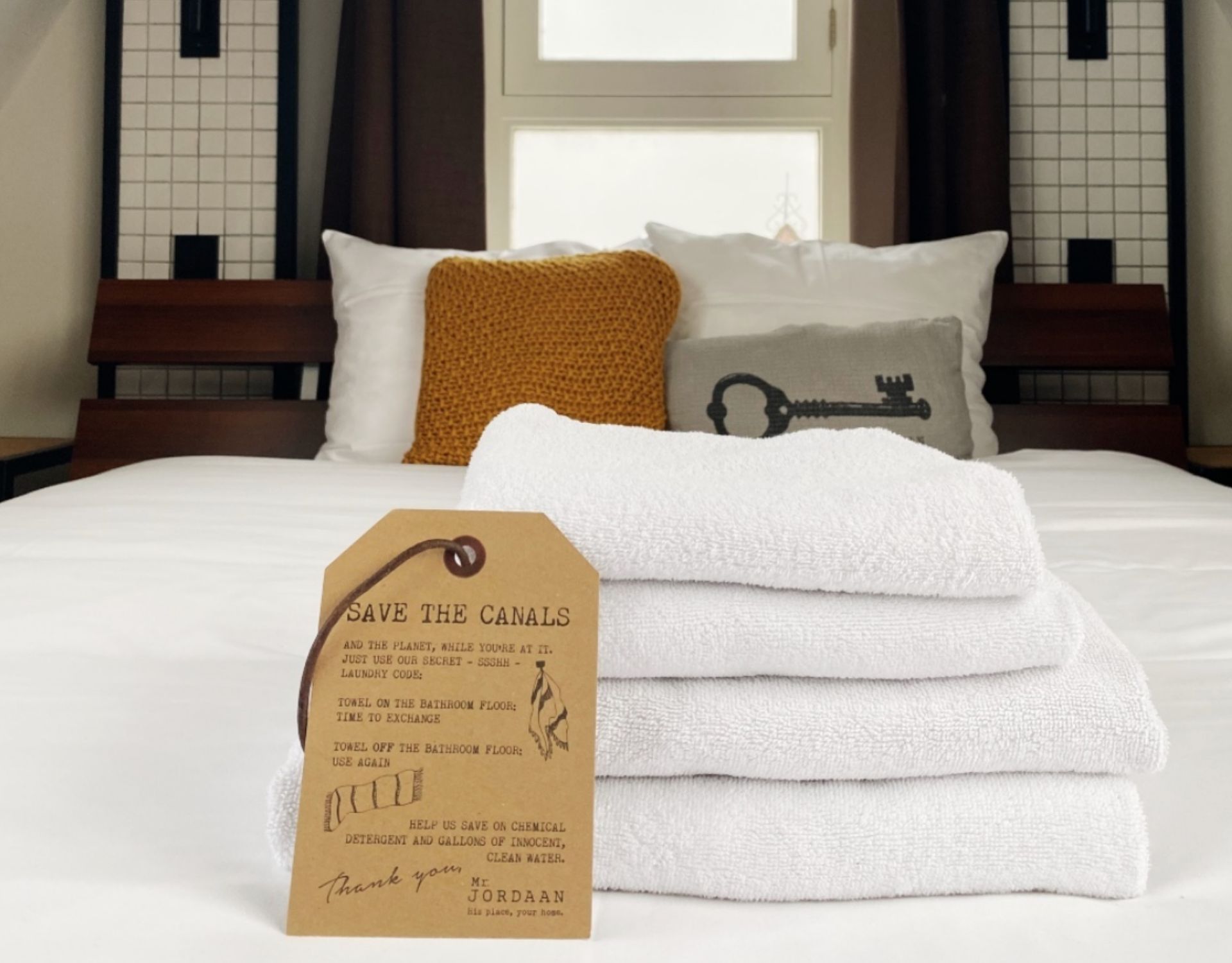 A canal sign on a stack of white towels on a bed with cushions in mr jordaan hotel amsterdam