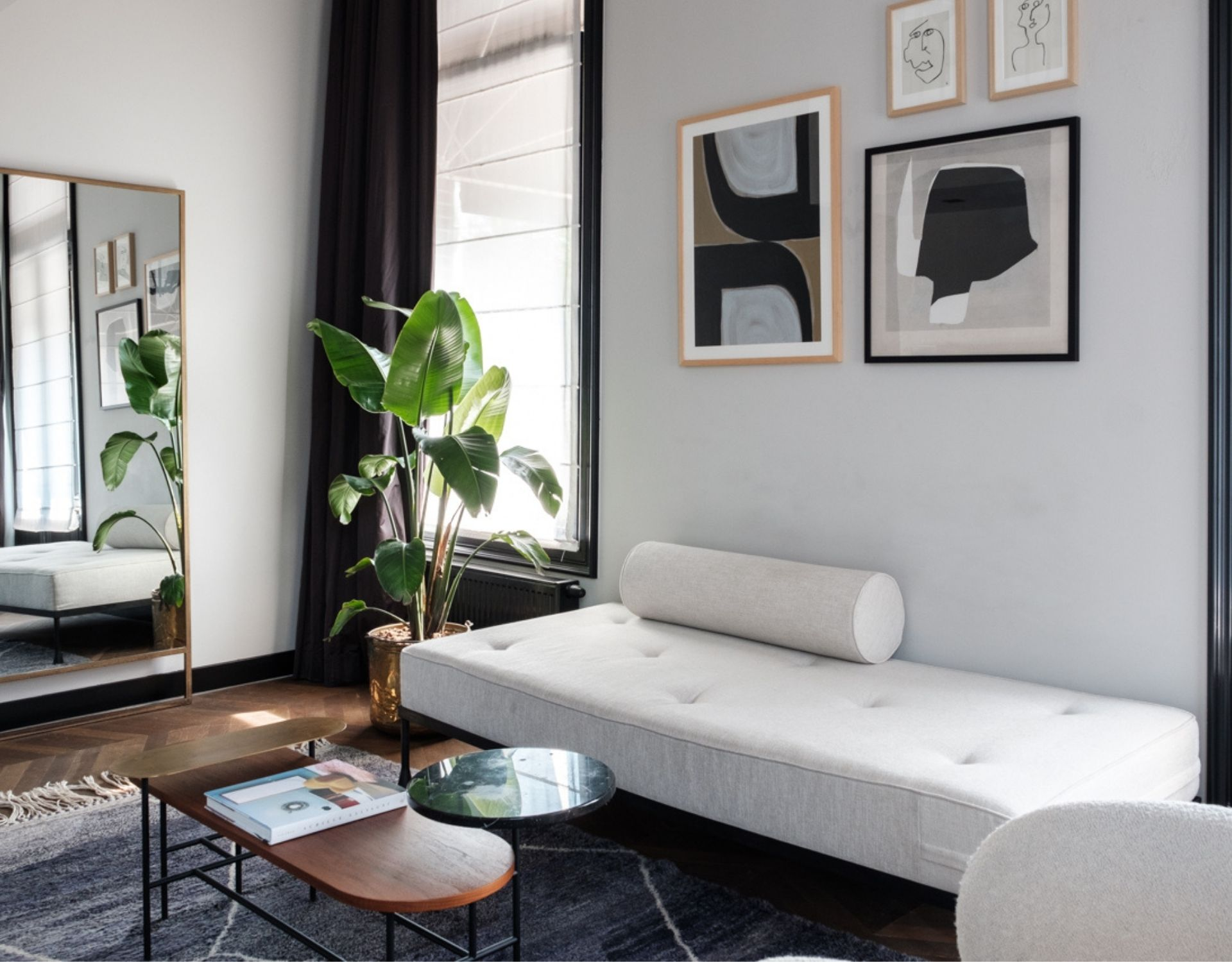 couch, magazine on coffee table with a mirror, plants and art on the wall